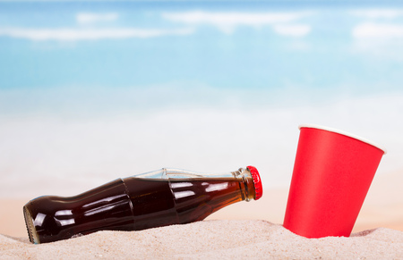 Bottle with a refreshing drink and a glass in the sand. Stock Photo