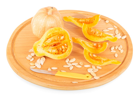 Wooden platter with whole and cut into pieces of pumpkin, sunflower seeds. Isolated on white background.