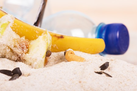 food waste: Cigarette butts, household and food waste in the sand on the seashore.