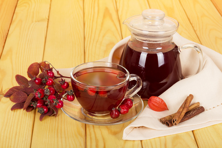 Jug and cup of rosehip drink, vanilla sticks on a background of light wood. Stock Photo
