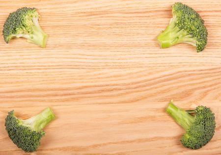 Fresh sliced broccoli pieces on the background of light wood.