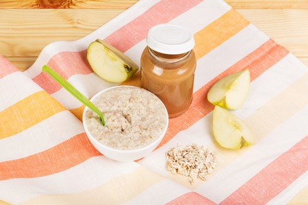 Food for children: applesauce and oatmeal on the background of light wood.