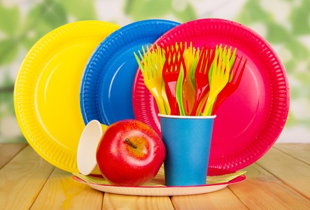 Bright, disposable tableware on abstract green background Stock Photo