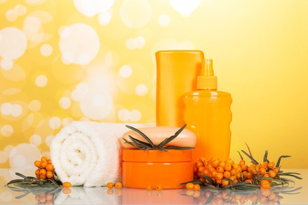 Towel and cosmetics from Sea buckthorn on abstract yellow background