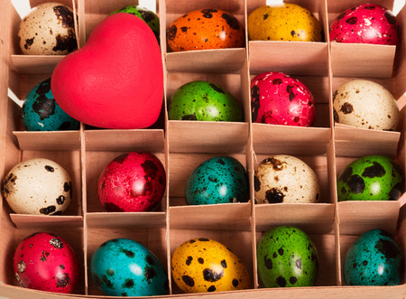 Colored Easter eggs in a box with cells and red heart. Background. Stock Photo
