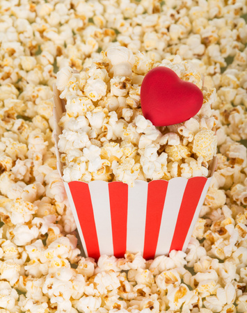 A large square box of popcorn and red heart, a lot of popcorn around. Background. Close-up.