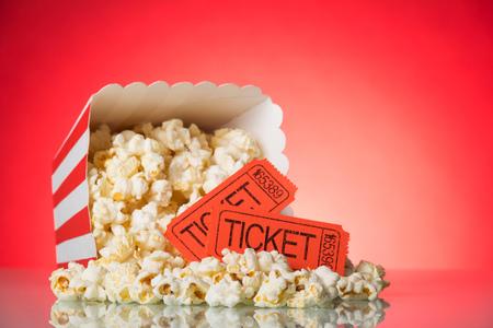 Una grande scatola quadrata con popcorn sbriciolato e biglietti per il cinema su uno sfondo rosso acceso.