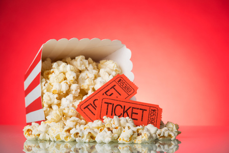 A large square box with crumbled popcorn and movie tickets on a bright red background.