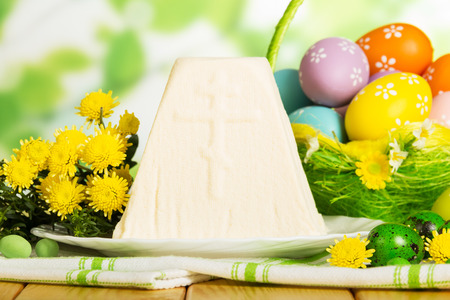 huevos de codorniz: Colored Easter eggs in the basket, traditional Easter cheesecake dessert on a cloth, herbs, candies on abstract green background. Close-up.