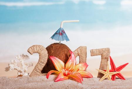 Čísla 217 navlečená vláknem, kokosem se slámou na pití a deštníkem, hvězdice a korály, květina v písku proti moři. Reklamní fotografie