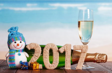 Digits 2017 twined with twine, snowman, champagne and New Years gifts on the table against the sea
