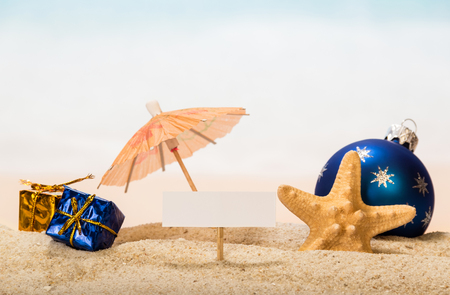 A blank card on a peg, an umbrella, a Christmas ball and gifts, a starfish in the sand against the background of the sea.