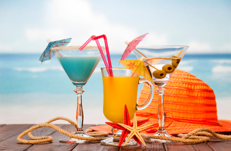 Cocktail, a glass of orange juice and alcohol with olives, a hat, starfish and twine on the background of the sea. Stock Photo