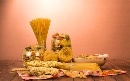 Banks with various pasta, spaghetti bunches, a bowl of farfalle and a shovel, nests of thin vermicelli and noodles on a red background.