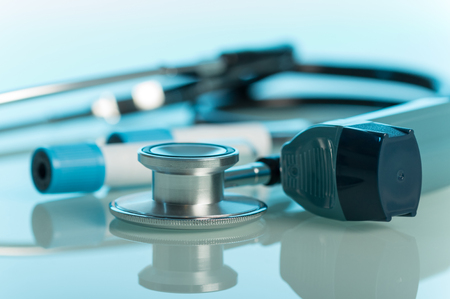 Small pocket inhaler, phonendoscope and test tubes on blue background Stock Photo