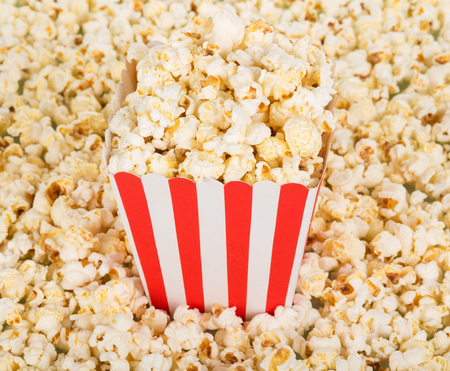 A large square box of popcorn and a lot of popcorn around. Background. Close-up.