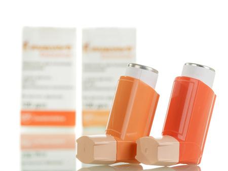 Twee van het astmainhaleertoestel en de verpakking van geneesmiddelen die op witte achtergrond worden geïsoleerd.