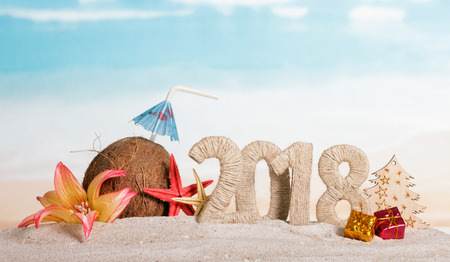 New Year inscription 2018, Christmas gifts and a Christmas tree, a coconut with a straw and umbrella, starfish, flower in the sand.