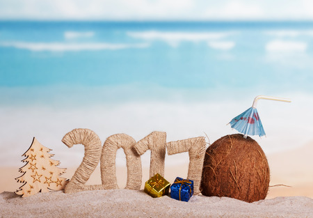 Figures 2017 twined with with string, coconut with a straw and the umbrella of, Christmas tree and gifts from a tree in the sand against the sea.
