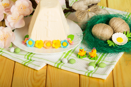 Easter cheese dessert on a plate decorated with flowers, Easter eggs wrapped with twine in the nest, Easter Bunny, toy chickens and candy on a background of light wood.