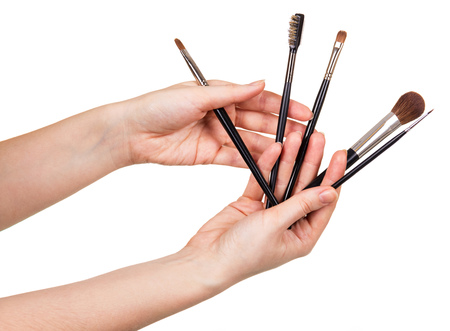 Various cosmetic brushes in female hands isolated on white background.