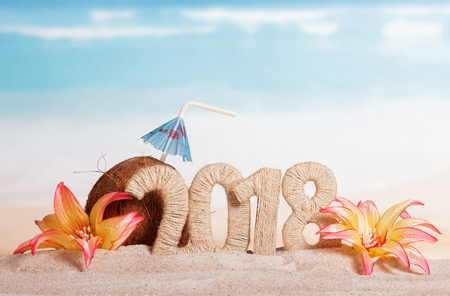 New Year inscription 2018, a coconut with a straw and an umbrella decorated with flowers on the sand.