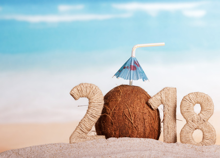 New Year inscription 2018, coconut with drinking straw and umbrella instead of the number 0 in the sand on the beach.
