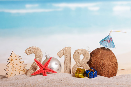 New Year inscription 2018, white Christmas ball instead of the number 0, the tree and the coconut with a straw, Christmas gifts, starfish on the sand.