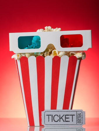 A large square box of popcorn, 3D glasses and movie ticket beside on a bright red background.