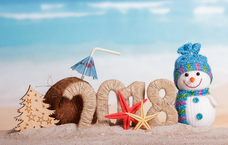 New Year inscription 2018, a snowman, a Christmas tree, a coconut with a straw and umbrella, starfish on the sand.