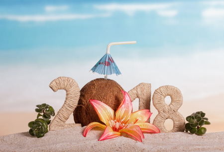 New Year inscription 2018, coconut with drinking straw and umbrella instead of the number 0, flower and green leaves on the sand.