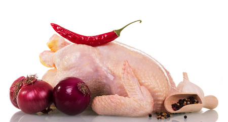 red onions: A whole raw chicken carcass, a scoop with various peppers and chili, garlic, onions isolated on white background. Stock Photo