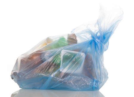 Blue plastic bag filled with household waste isolated on white background.
