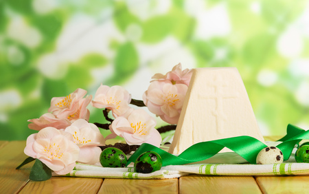 religious event: The traditional Easter dessert curds and eggs on a cloth, flowers, ribbon on abstract green background.
