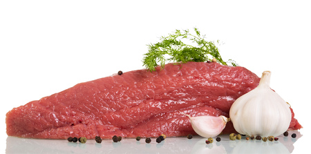 A piece of raw beef, spices, garlic and dill isolated on white background. Banco de Imagens