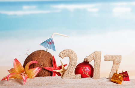 217 Digits twined with twine, Christmas ball instead of the digits 0, coconut, sea stars, gifts and flower in the sand against the sea.