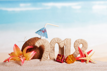 New Year inscription 2018, Christmas gifts, coconut with drinking straw and umbrella, starfish, flower in the sand.