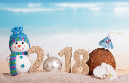 New Year inscription 2018, white Christmas ball instead of the number 0, a coconut with a straw, snowman and Orchid flower on the sand.