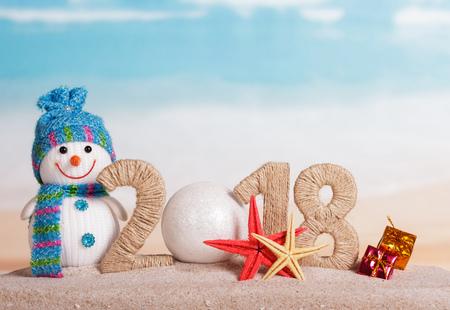 Nový rok 2018 nápis, namísto čísla 0 - bílá koule, sněhulák, dárky a hvězdice v písku na pláži. Reklamní fotografie