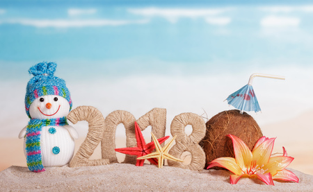 New Year inscription 2018, coconut with drinking straw and umbrella, snowman, flower, and starfish in the sand on the beach. Stock Photo