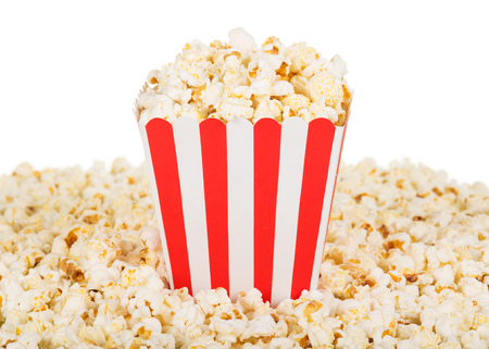 A large square box of popcorn and popcorn are many around, isolated on white background. Close-up.