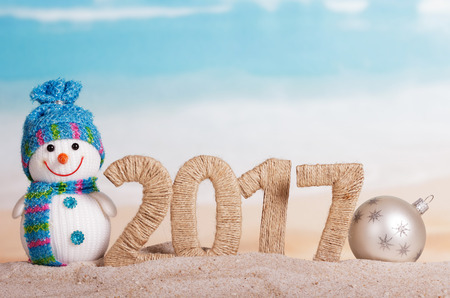 Digits 2017 twined string, snowman and new year ball in the sand against the sea.