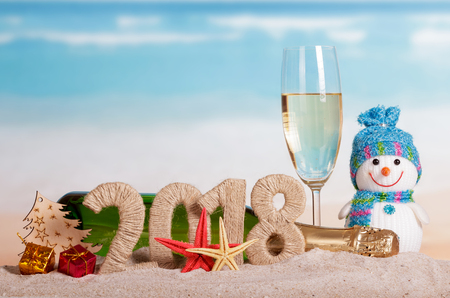 New Year inscription 2018, a bottle and a glass of champagne, snowman, gifts, Christmas ball, Christmas tree and starfish in the sand. Foto de archivo