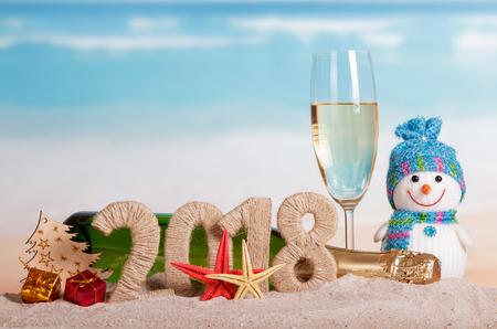 Nový rok 2018 nápis, láhev a sklenici šampaňského, sněhulák, dárky, vánoční koule, vánoční stromek a hvězdice v písku. Reklamní fotografie