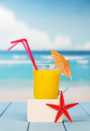 A glass of orange juice with an umbrella and straws, an empty card and a starfish against the background of the sea. Stock Photo