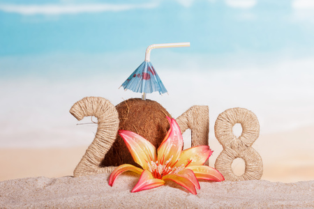 New Year inscription 2018, coconut with drinking straw and umbrella instead of the number 0, a flower in the sand on the beach.
