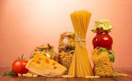 Vázané špagety jsou umístěny svisle, hnízdo tenkých vermicelli, dvě sklenice s různými těstovinami, láhev kečupu, rajčata, sýr na červeném pozadí.