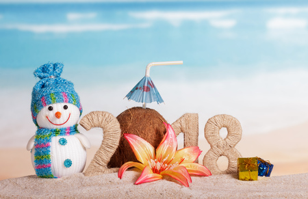New Year inscription 2018, coconut with drinking straw and umbrella instead of the number 0, snowman, gifts and flower in the sand.