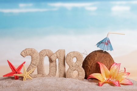 New Year inscription 2018, coconut with drinking straw and umbrella, flower, and starfish in the sand on the beach.