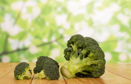Ripe inflorescences of broccoli on an abstract green background.